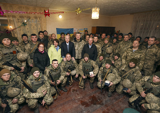 Ukrainian President Petro Poroshenko centre, Chairman of Senate Armed Services Committee, US Senator John McCain, centre left, US Senator Lindsey Graham, centre right, and US Senator Amy Klobuchar pose for photo with the Ukrainian marines, during their working trip to the Donetsk region to congratulate Ukrainian servicemen on the upcoming New Year, in the village Shyrokine, eastern Ukraine, Saturday, Dec. 31, 2016