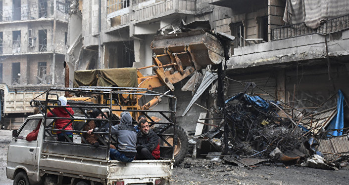 Syrian civilians drive past a tractor removing rubble as the Syrian government starts to clean up areas formerly held by opposition forces in the northern city of Aleppo on December 27, 2016, in the Shaar district.