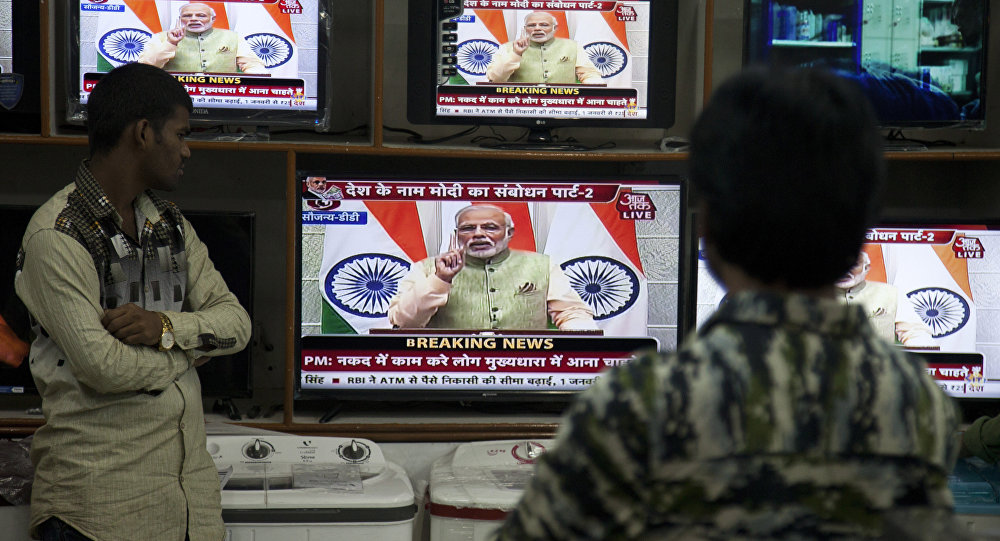 People watch Indian Prime Minister Narendra Modi addressing the nation, on television in Hyderabad, India, Saturday, Dec. 31, 2016