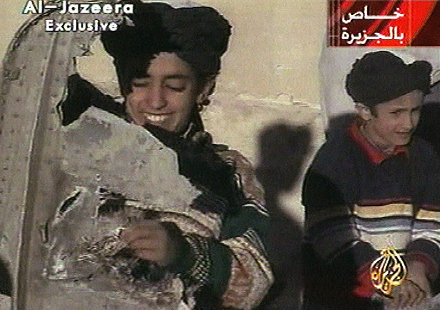 In this image made from video broadcast by the Qatari-based satellite television station Al-Jazeera Wednesday, Nov. 7, 2001, a young boy, left, identified as Hamza bin Laden holds what the Taliban says is a piece of U.S. helicopter wreckage in Ghazni, Afghanistan on Monday, Nov. 5, 2001