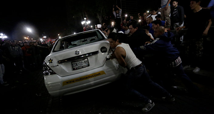 Demonstrators push over a vehicle of Multimedios TV network during a protest against the rising prices of gasoline enforced by the Mexican government at the Macroplaza in Monterrey, Mexico, January 5, 2017