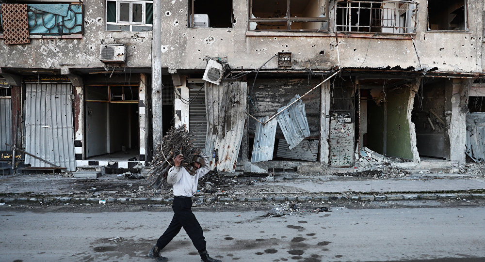 A Syrian man carries wood to be used for heating in the rebel-held town of Douma, on the eastern outskirts of Damascus