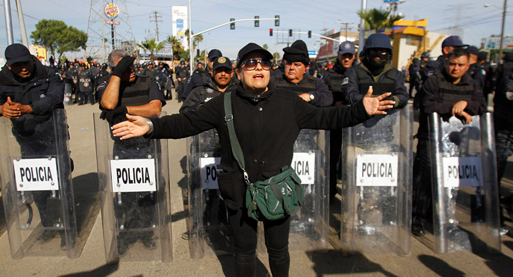 A demonstrator gestures in front of policemen as a group of them blocked the entrance of a Pemex gas storage station during a protest against the rising prices of gasoline enforced by the Mexican government, in Rosarito, Mexico, January 7, 2017.