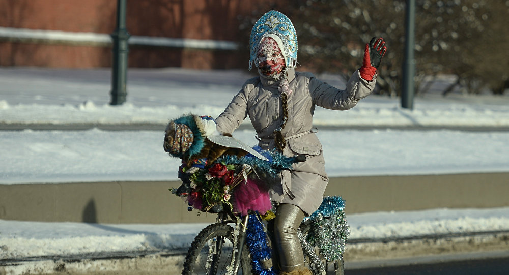 A participant in the Second Winter Bicycle Parade dressed as Snow Maiden, near Red Square, in Moscow.