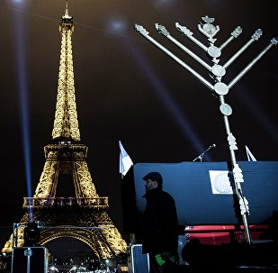 A member of the Jewish community stands near a Menorah (Hanukkah), a nine-branched candelabrum, before the lighting of two branches in front of the Eiffel tower in Paris on December 25, 2016.