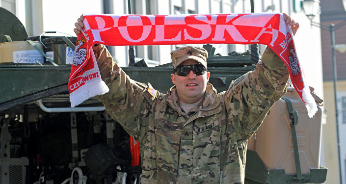 Sgt Robert Snyder from the 3rd Squadron of the 2nd Cavalry Regiment waves a scarf with the inscription Poland as a group of Stryker armored vehicles stop on the Kosciuszko Market Square to meet residents in Bialystok, Poland, Tuesday, March 24, 2015