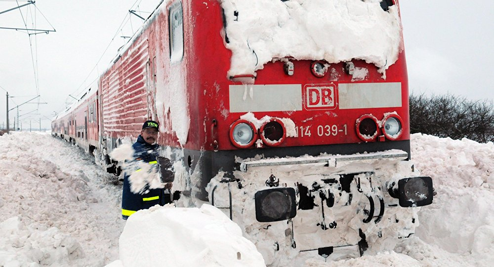 A worker shovels snow at a railway train that is stocked in the snow near Anklam, northern Germany (File)