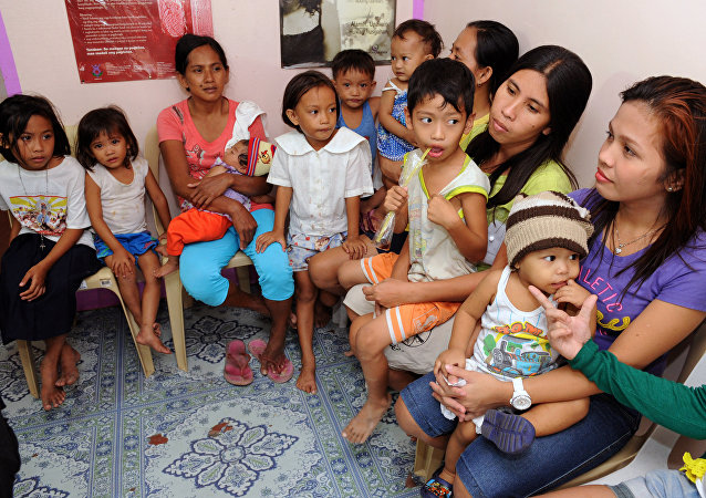 In this photo taken January 16, 2013, a health worker (C) shows an intrauterine device (IUD) to mothers at the Likhaan Center for Women's Health in Baseco, a massive slum in Manila where more than 60,000 people compete for space.
