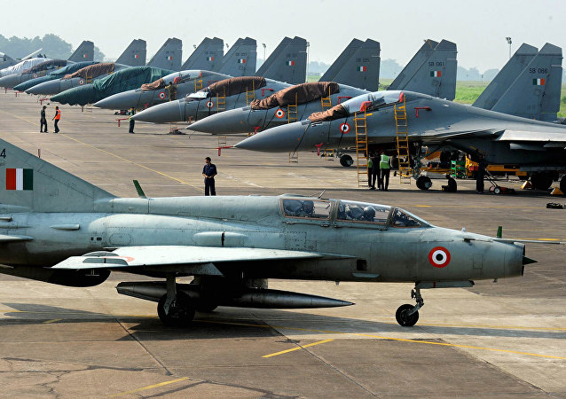 An Indian Air Force (IAF) MIG-21 passes near Sukhoi-30 fighter jets before a drill for Air Force Day celebrations in Kalikunda IAF airbase around 170 km west of Kolkata.