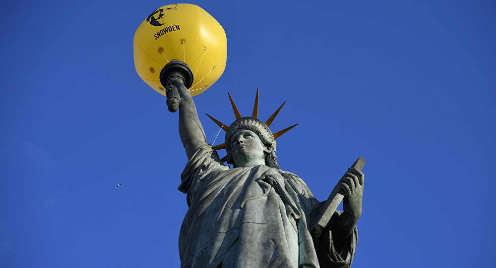 A balloon bearing the effigy of former US intelligence contractor and whistle blower Edward Snowden is seen attached to the Statue of Liberty replica by French sculptor Auguste Bartholdi (1834-1904) during an action organized by human rights organisation Amnesty International (AI) asking outgoing President Barack Obama to pardon him, on January 13, 2017 in Paris