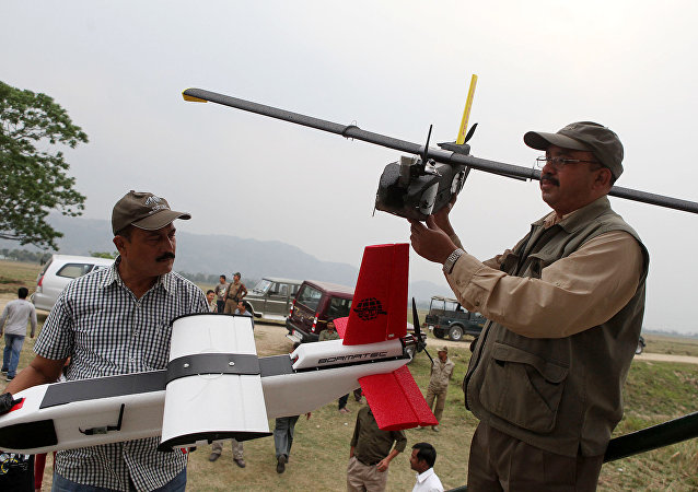 Indian forestry officials hold up unmanned aerial vehicles (UAV) during a demonstration.