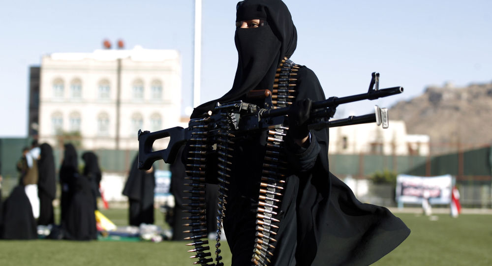 A Yemeni female fighter supporting the Shiite Huthi rebels, and carrying weapons used for ceremonial purposes, takes part in an anti-Saudi rally in the capital Sanaa