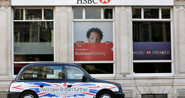 A taxi drives past a branch of HSBC bank in London, Britain, February 9, 2015.