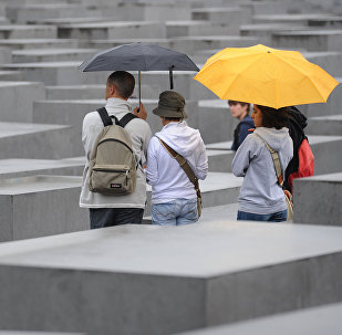 Tourists with umbrellas walk through the Holocaust Memorial on July 28, 2011 in Berlin.