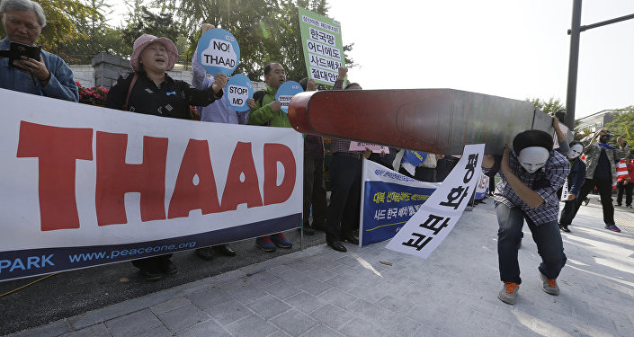 Protesters carry a mock missile symbolizing an advanced U.S. missile defense system called Terminal High-Altitude Area Defense, or THAAD, during a rally to oppose a plan to deploy the THAAD in front of the Defense Ministry in Seoul, South Korea, Thursday, Oct. 20, 2016