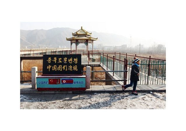 A tourist stands by a bridge connecting Chinese and North Korean border cities