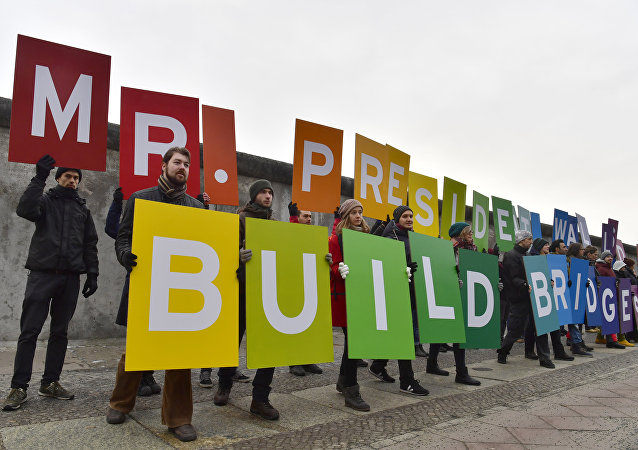 Activists from Greenpeace display a message reading Mr. President, walls divide. Build Bridges! along the Berlin wall in Berlin on January 20, 2017 to coincide with the inauguration of Donald Trump as the 45th president of the United States