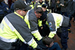 Police try to remove a demonstrator from attempting to block people entering a security checkpoint, Friday, Jan. 20, 2017, ahead of President-elect Donald Trump's inauguration in Washington