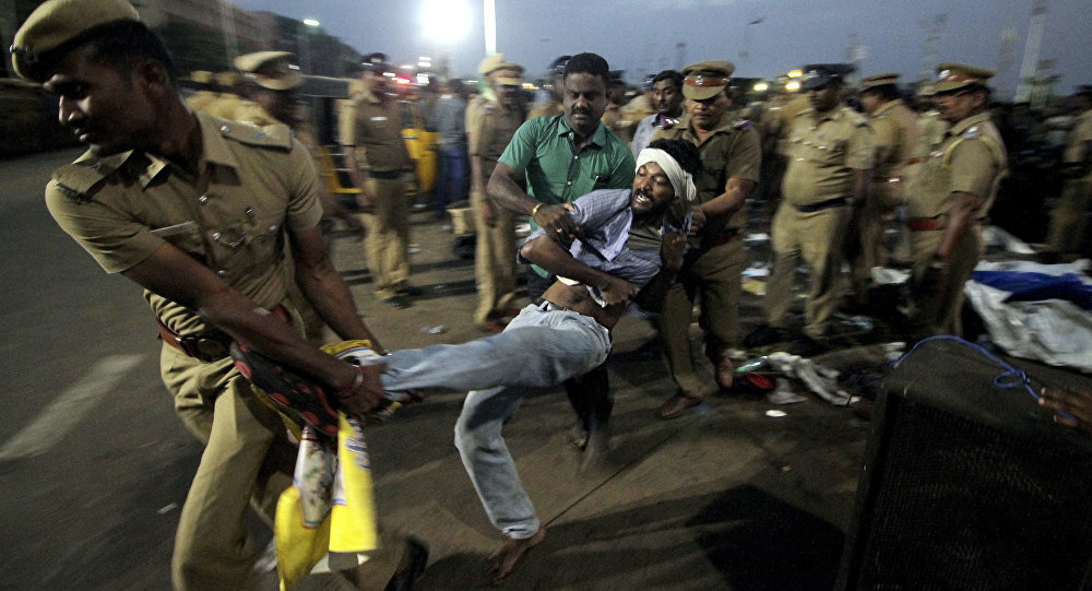 A protestor supporting Jallikattu, a traditional bull-taming ritual tries to resist as police remove them from the Marina beach on the Bay of Bengal coast in Chennai, India, Monday, Jan.23, 2017.