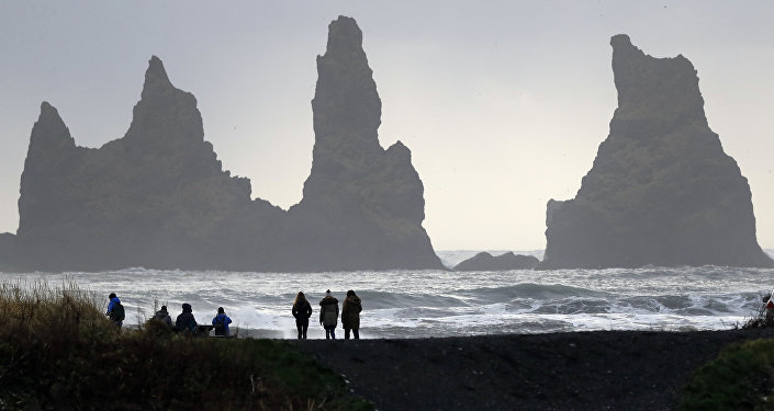 People walk on the black sanded beach in Vik, Iceland, near the Volcano Katla