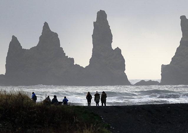 People walk on the black sanded beach in Vik, Iceland, near the Volcano Katla