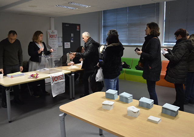 People prepare to vote at a polling station during the second round of the left-wing primary for the 2017 French presidential election, on January 29, 2017 in Toulouse, southern France
