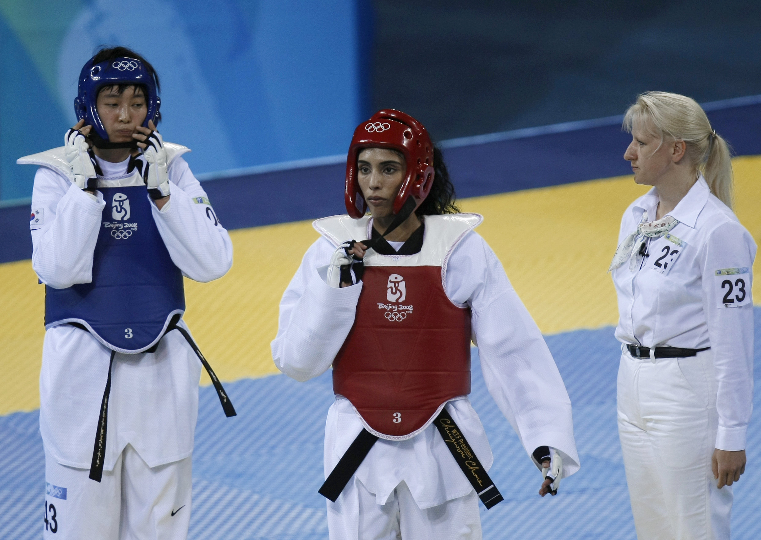 United Arab Emirates Princess Sheikh Maitha Almaktoum (C) walks after her match with Kyungseon Hwang of South Korea (L) during their women's -67 kg taekwondo priliminary at the 2008 Beijing Olympic Games in Beijing on August 22, 2008