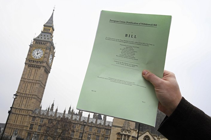 A journalist poses with a copy of the Brexit Article 50 bill, introduced by the government to seek parliamentary approval to start the process of leaving the European Union, in front of the Houses of Parliament in London, Britain, January 26, 2017