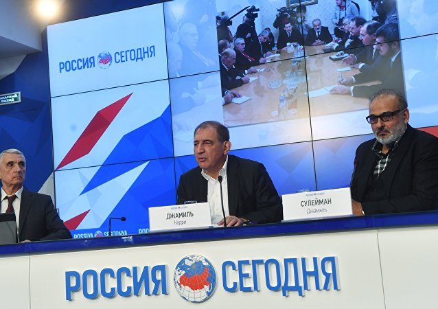 Qadri Jamil, center, chairman of the Syrian opposition's Moscow group, secretary of the People's Will Party and one of the leaders of the Popular Front for Change and Liberation, with Jamal Suleiman, right, a representative of the Syrian opposition's Cairo group, during a news conference at the Rossiya Segodnya International Multimedia Press Center in Moscow