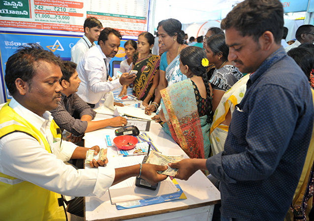 An Indian visitor (R) receives cash from a bank employee after withdrawing money from his bank account with his Aadhaar or Unique Identification (UID) card during a Digi Dhan Mela, held to promote digital payment, in Hyderabad on January 18, 2017