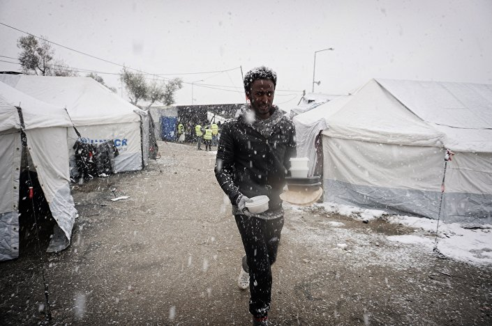 A migrant walks after receiving food during snowfall at the Moria hotspot on the Greek island of Lesbos, on January 9, 2017.