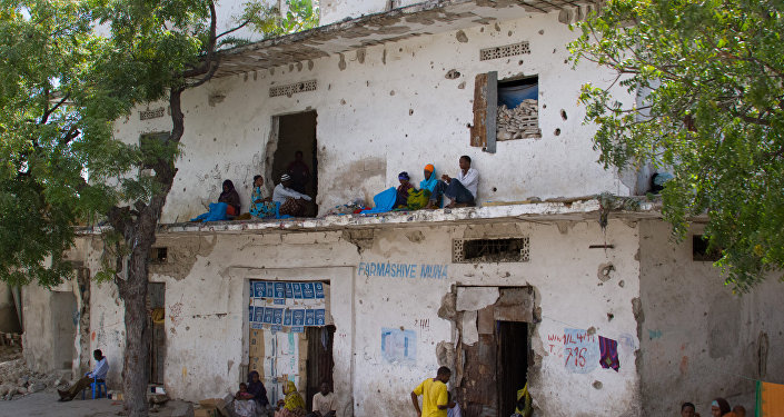 People rest along a bullet-ridden building in Mogadishu, Somalia