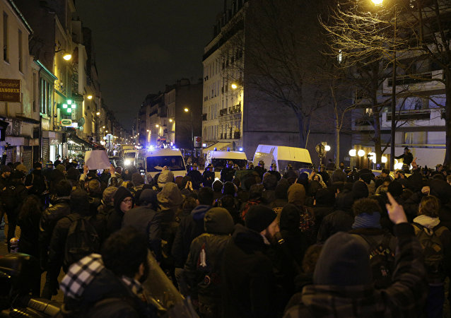 Police block a street as people gather to protest against an alleged police assault on a black man while in custody in central Paris