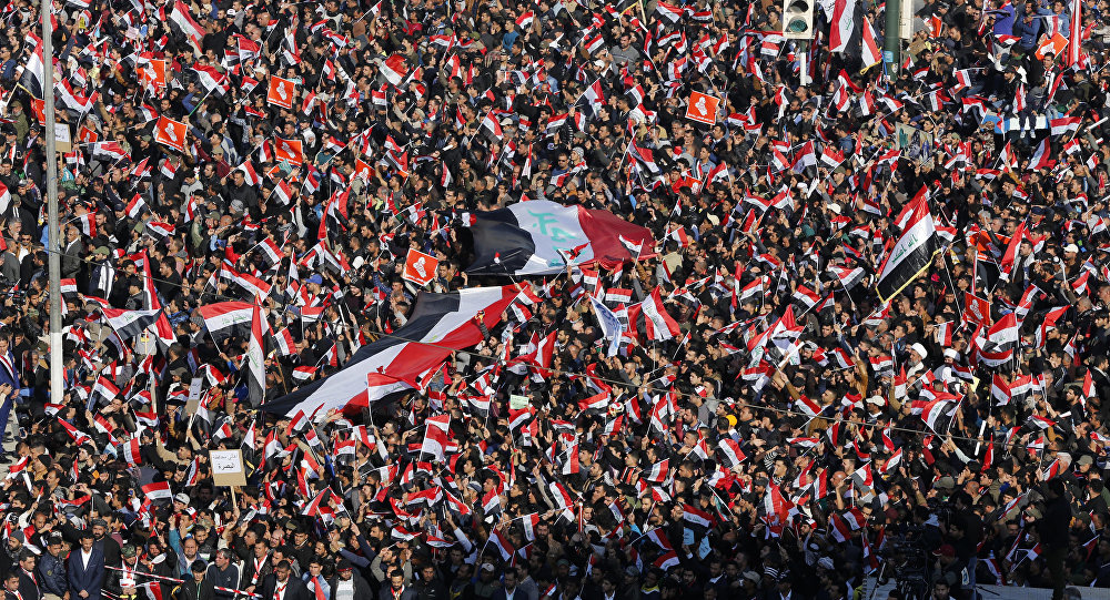 Followers of Iraq's influential Shiite cleric Muqtada al-Sadr chant slogans as they wave national flags during a demonstration against corruption in Baghdad, Iraq