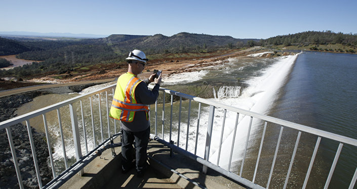 In this Saturday, Feb. 11, 2017, photo, Jason Newton, of the Department of Water Resources, takes a picture of water going over the emergency spillway at Oroville Dam in Oroville, Calif