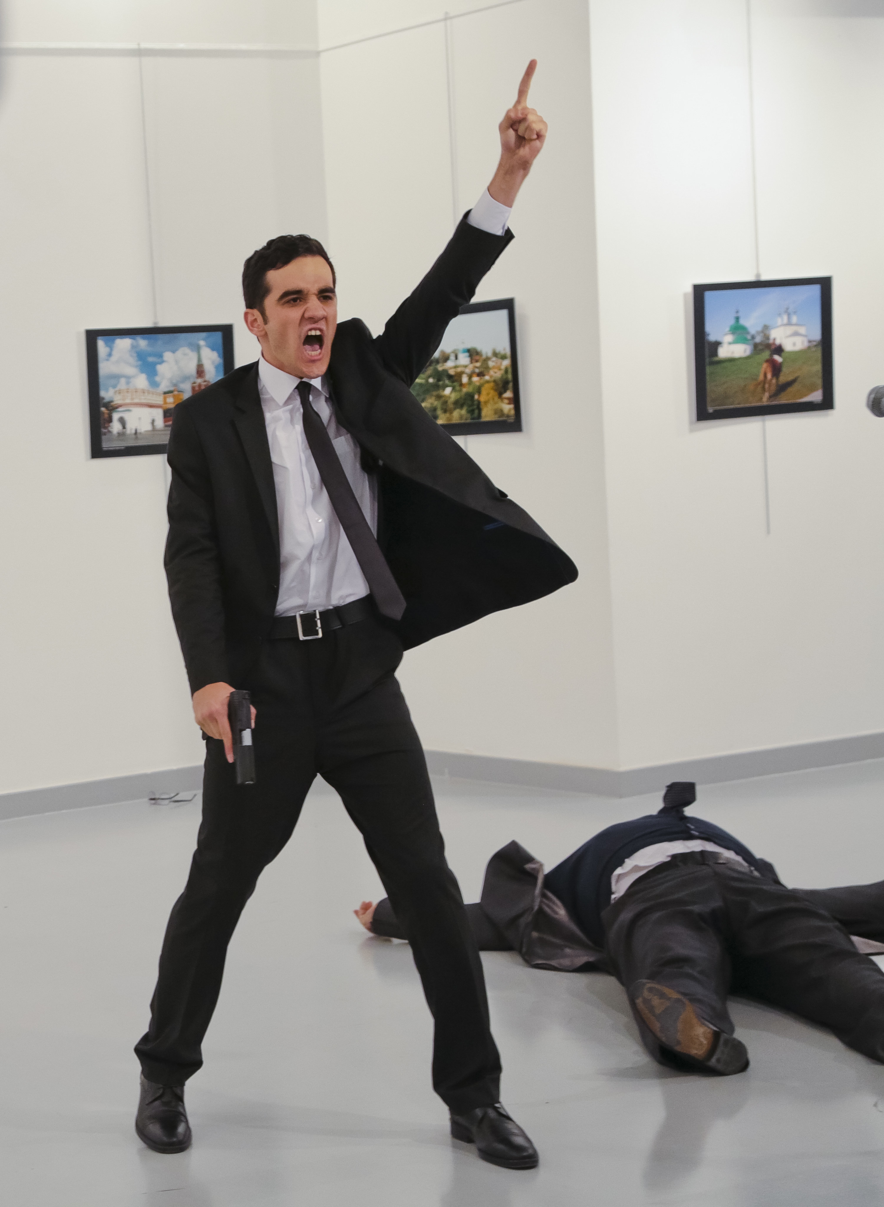 In this Monday, Dec. 19, 2016 file photo, Mevlut Mert Altintas shouts after shooting Andrei Karlov, right, the Russian ambassador to Turkey, at an art gallery in Ankara, Turkey