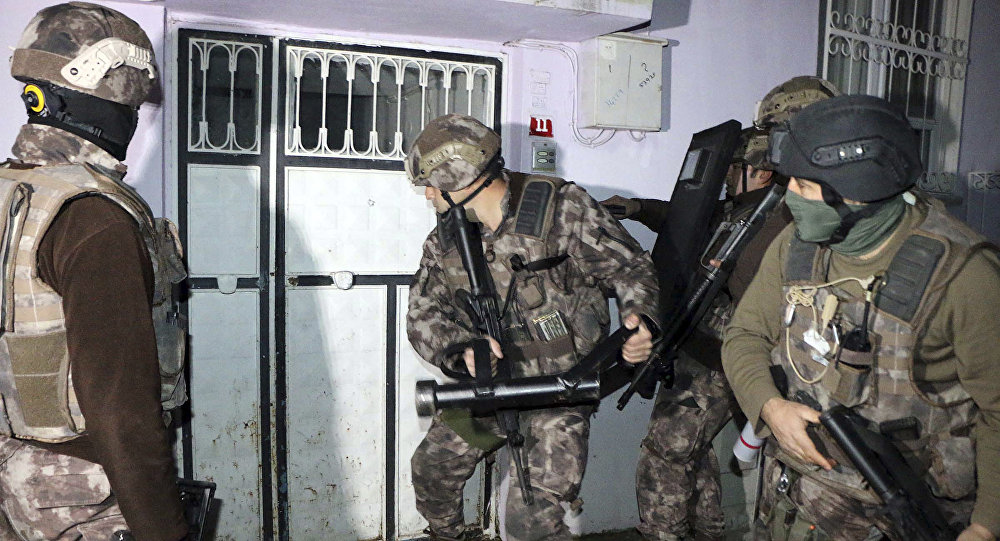 Turkish anti-terrorism police break a door during an operation to arrest people over alleged links to the Islamic State group, in Adiyaman, southeastern Turkey, early Sunday, Feb. 5, 2017