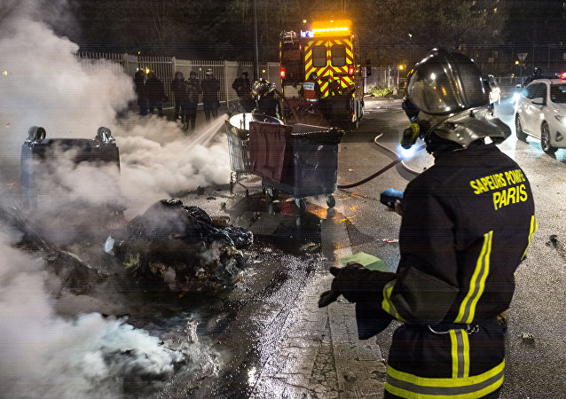 Firefighters extinguish garbage containers set ablaze during the unrest following a protest against police brutality in the Paris suburb of Bobigny. file photo