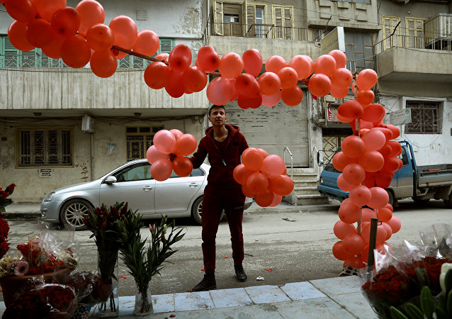 A Syrian man arranges balloons in front of a shop selling Valentine's day gifts in the northeastern city of Qamishli on February 13, 2017