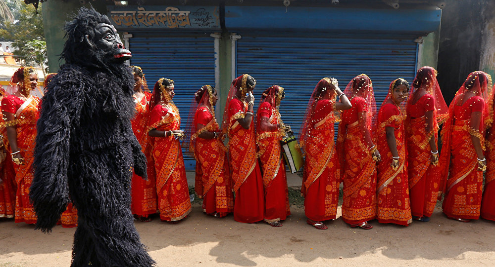 A performer dressed in a chimpanzee costume walks past brides as they arrive at a mass marriage ceremony in which, according to its organizers, 109 tribal, Muslim and Hindu couples from various villages across the state took their wedding vows, at Bahirkhand village, north of Kolkata, India February 5, 2017