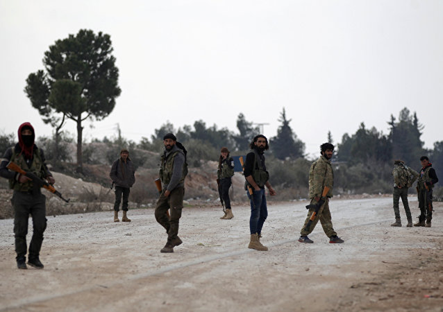 Free Syrian Army fighters carry their weapons as they stand on the outskirts of the northern Syrian town of al-Bab, Syria.