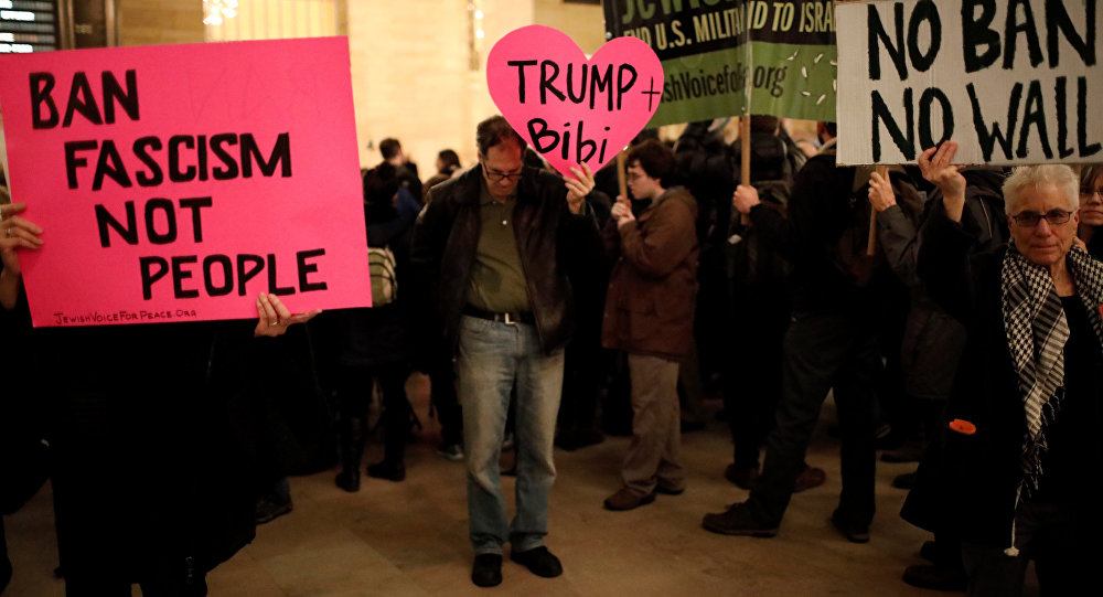 Demonstrators hold signs during a Muslim and Jewish Solidarity protest against the policies of U.S. President Donald Trump and Israeli Prime Minister Benjamin Netanyahu at Grand Central Terminal in New York City, U.S.