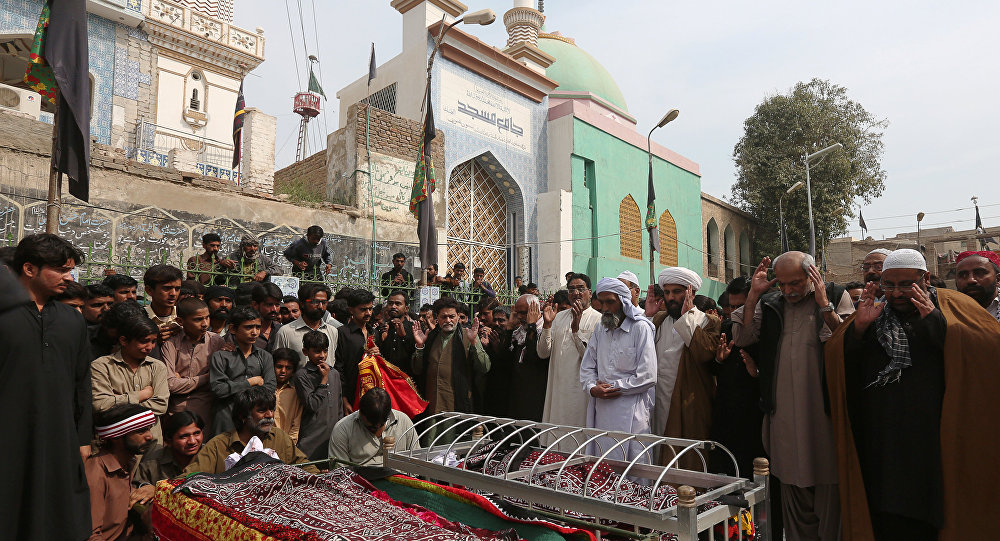 Men and relatives gather to attend funeral prayers for victims killed in a suicide blast at the tomb of Sufi saint Syed Usman Marwandi, also known as the Lal Shahbaz Qalandar shrine, during a funeral in Sehwan Sharif, Pakistan's southern Sindh province