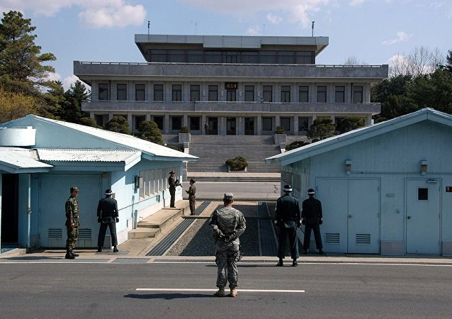 A view from South Korea towards North Korea in the Joint Security Area at Panmunjom. North and South Korean military personnel, as well as a single US soldier, are shown