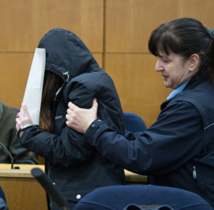 One of the main defendants covers the face as she enters the courtroom for the trial on charges of exorcism at court in Frankfurt am Main, on February 20, 2017