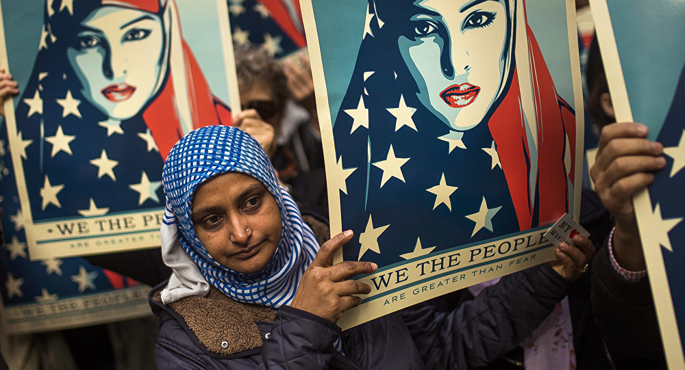 People carry posters during a rally against President Donald Trump's executive order banning travel from seven Muslim-majority nations, in New York's Times Square, Sunday, Feb. 19, 2017.