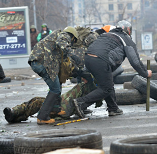 Anti-government protestors evacuate a comrade wouned by a sniper during clashes with the police in the center of Kiev on February 20, 2014