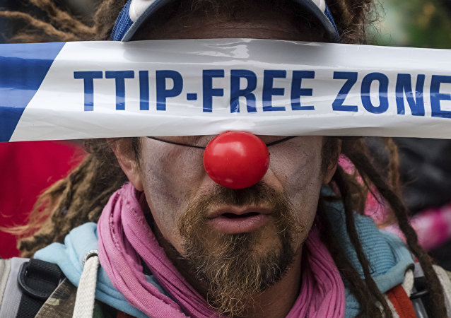 A man covers his eyes with a banner as he protests against international trade agreements TTIP and CETA in front of EU headquarters in Brussels on Thursday, Oct. 27, 2016