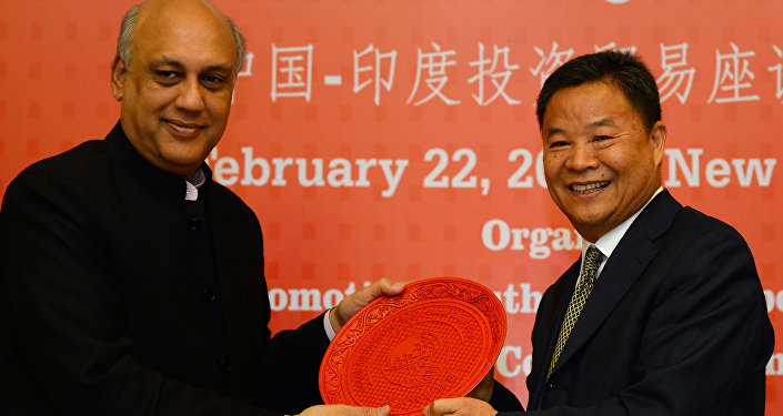 Vice chairman of the CPPCC Foreign Affairs Committee Lu Xinhua (R) is presented a memento by former Federation of Indian Chambers of Commerce and Industry (FICCI) president and current chairman of XPRO India Sidharth Birla at a China-India business meeting for investment and trade at Federation of Indian Chambers of Commerce and Industry in New Delhi on February 22, 2017.