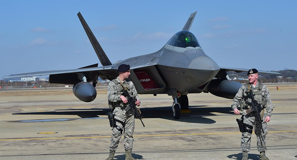 US soldiers stand guard near a US F-22 stealth fighter at the Osan Air Base in Pyeongtaek, south of Seoul, on February 17, 2016.